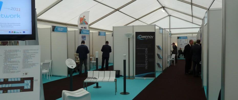 Salon professionnel avec exposants et stands modulaires de différentes dimensions en mélaminé, avec moquette