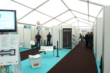 Salon professionnel avec exposants et stands modulaires de différentes dimensions en mélaminé, avec moquette.